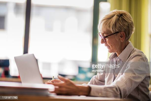 smiling senior teacher taking notes in the classroom. - professor stock pictures, royalty-free photos & images