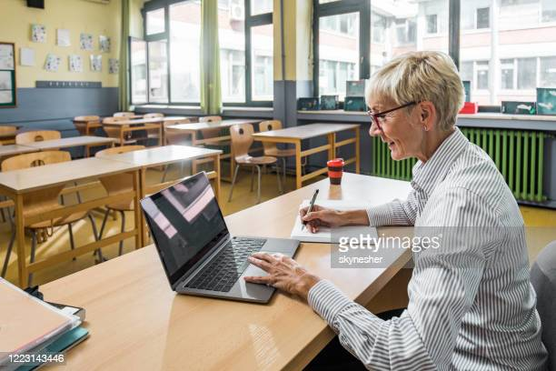 smiling senior teacher taking notes while using laptop in the classroom. - instructor stock pictures, royalty-free photos & images