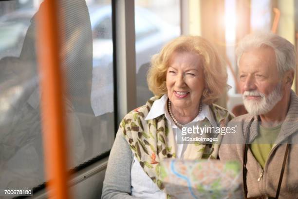 Leende senior turist i bussen