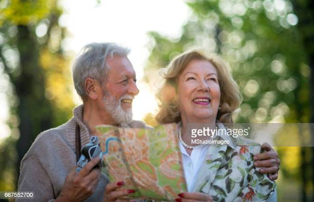 Smiling senior tourist using map