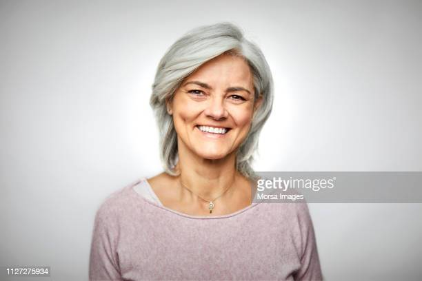 smiling senior woman against white background - portrait classique photos et images de collection