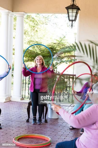 Glimlachend senior vrouw aan een fitness-klasse houden een kunststof hoepel op schouderhoogte