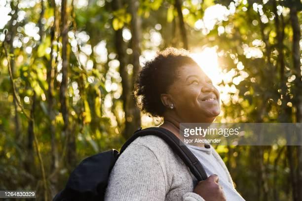 自然の中で日没時に笑顔の先輩女性 - エコツーリズム ストックフォトと画像