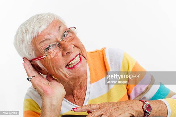 Smiling senior woman cupping her ear to listen