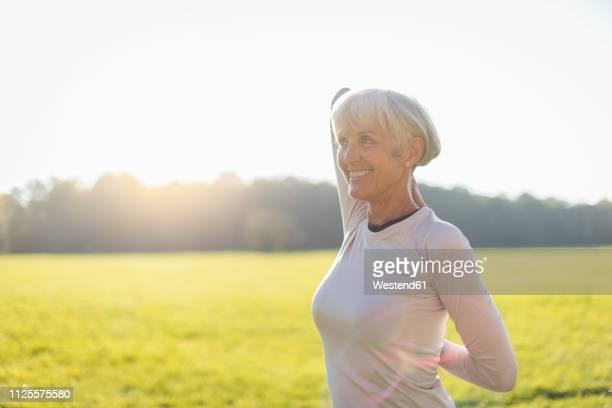 smiling senior woman doing gymnastics on rural meadow - 後ろ手 ストックフォトと画像
