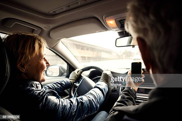 Smiling senior woman driving car while sitting by man taking selfie through smart phone