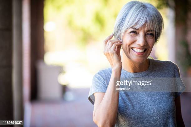 smiling senior woman during workout - satisfaction stock pictures, royalty-free photos & images