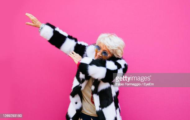 smiling senior woman gesturing against colored background - 年配の女性一人 ストックフォトと画像