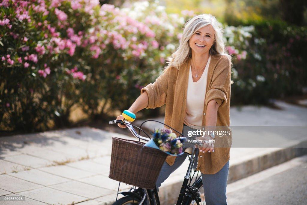 Donna anziana sorridente che si diverte a guidare una bici d'epoca in primavera : Foto stock