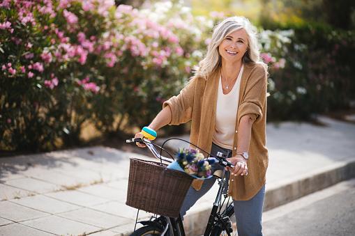 Smiling senior woman having fun riding vintage bike in spring - gettyimageskorea