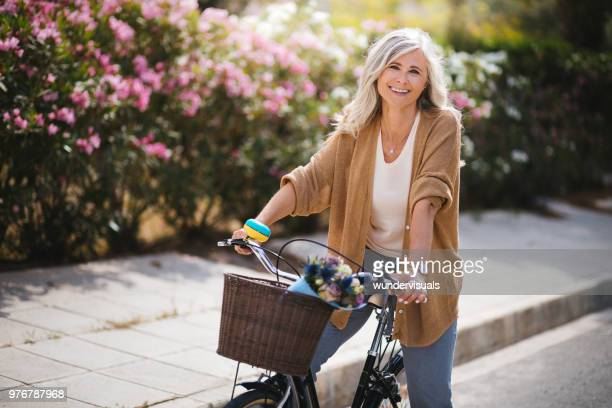 smiling senior woman having fun riding vintage bike in spring - mulheres maduras imagens e fotografias de stock