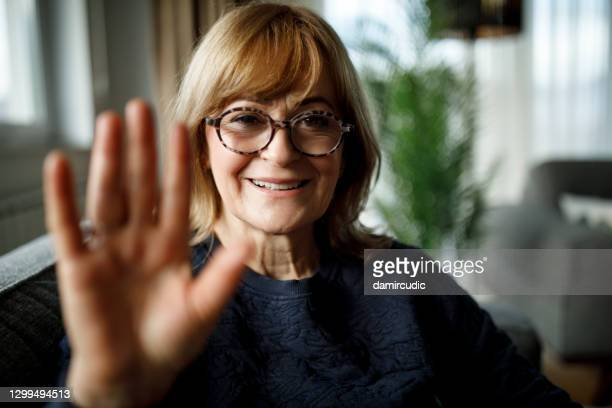 smiling senior woman having video call at home - waving stock pictures, royalty-free photos & images