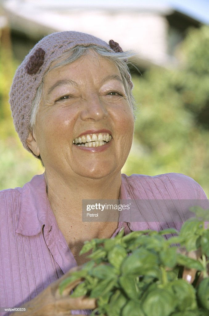 Smiling senior woman holding basil plants, close up : Foto de stock