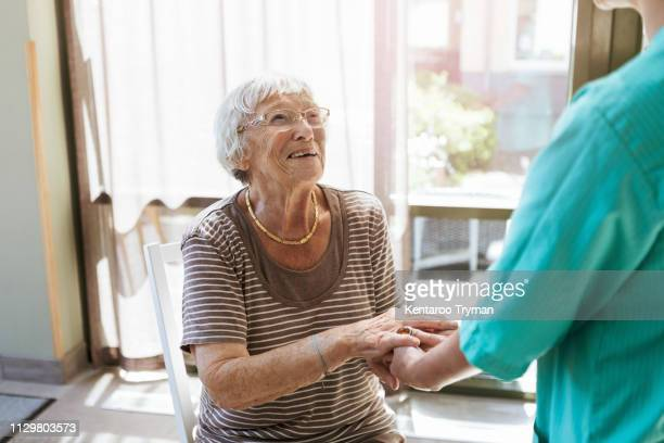smiling senior woman holding hands of healthcare worker at nursing home - asistir fotografías e imágenes de stock