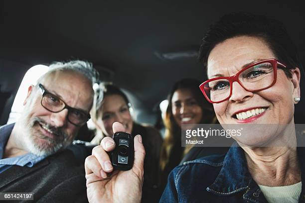 Smiling senior woman holding remote while sitting with people in car