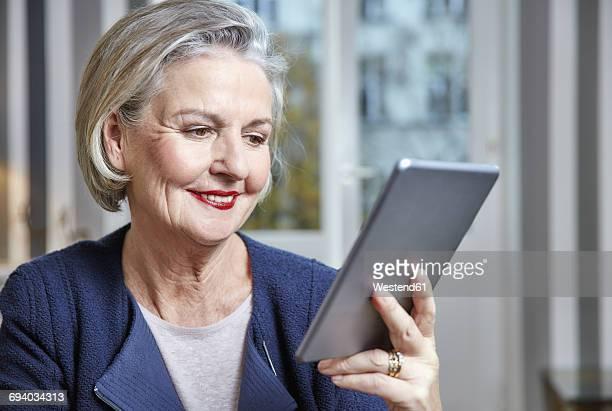 Smiling senior woman holding tablet
