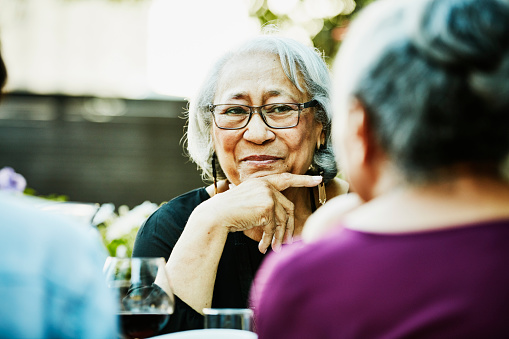 Smiling senior woman in discussion with family during outdoor dinner party - gettyimageskorea
