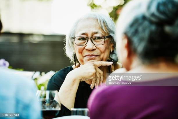 smiling senior woman in discussion with family during outdoor dinner party - listening stock pictures, royalty-free photos & images