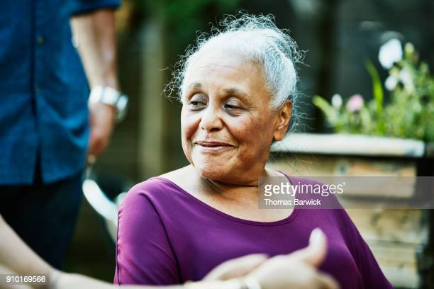 smiling senior woman in discussion with family members before outdoor dinner party - purple shirt stock photos and pictures