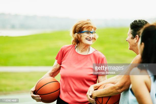 smiling senior woman in discussion with friends after basketball game on outdoor court - disruptaging stock photos and pictures