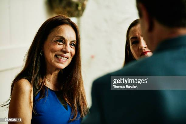 smiling senior woman in discussion with friends during cocktail party - 60 64 años fotografías e imágenes de stock
