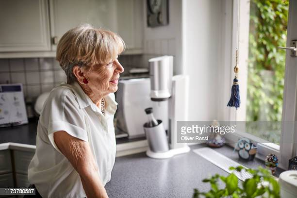 smiling senior woman in kitchen at home looking out of window - personal accessory stock pictures, royalty-free photos & images