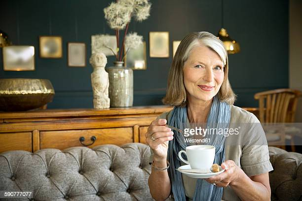 Smiling senior woman in lounge room with cup of coffee