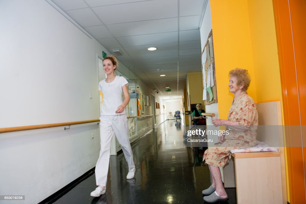 Smiling Senior Woman In The Retirement Home Waiting In The Corridor : Stock Photo