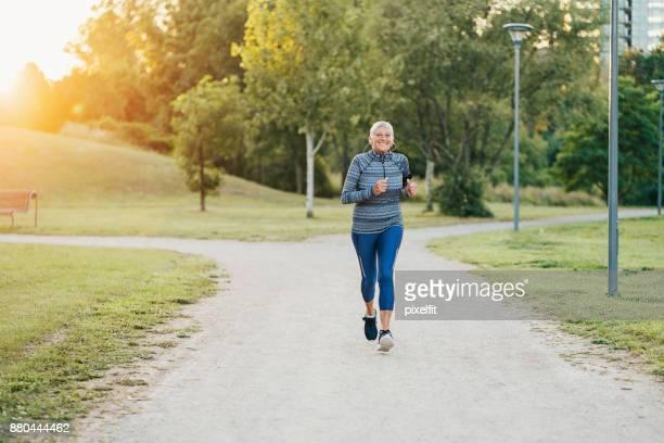 Smiling senior woman jogging in the park
