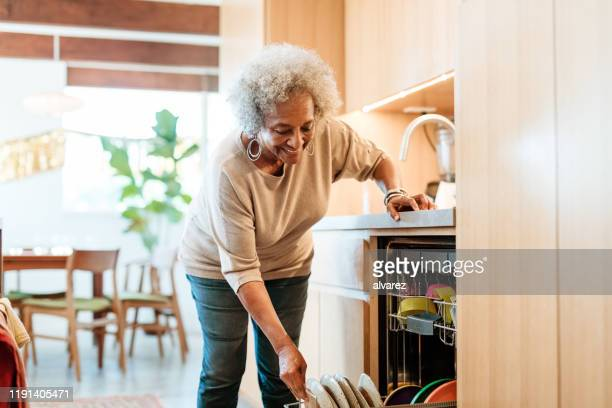 smiling senior woman keeping plates in dishwasher - bending stock pictures, royalty-free photos & images
