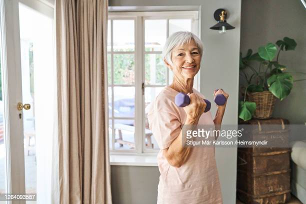 smiling senior woman lifting dumbbells while working out at home - hand weight stock pictures, royalty-free photos & images