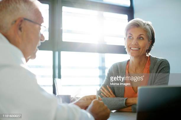 smiling senior woman looking at elderly doctor - visit stock pictures, royalty-free photos & images