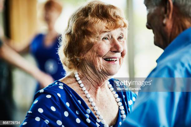 smiling senior woman looking at husband while dancing in ballroom - ballroom stock pictures, royalty-free photos & images