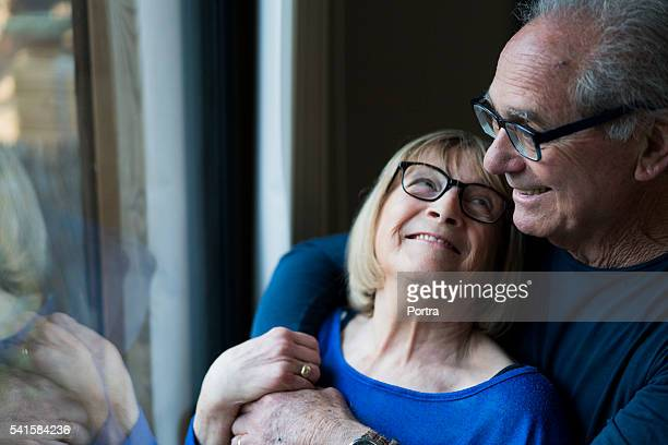 smiling senior woman looking at man by window - 60 69 years stock photos and pictures