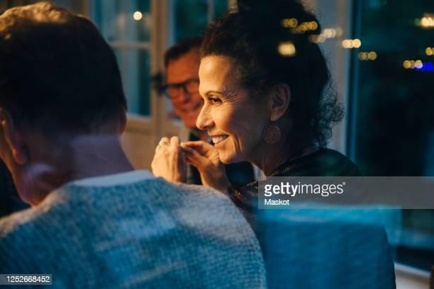 smiling senior woman looking at man during dinner party - evening meal stockfoto's en -beelden