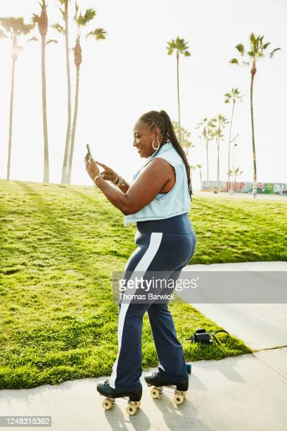 smiling senior woman looking at smart phone while roller skating in park - disruptaging stock pictures, royalty-free photos & images
