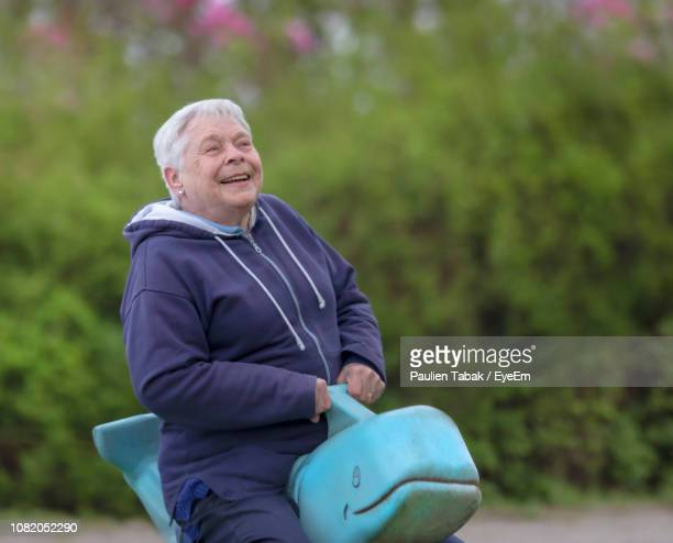 smiling senior woman looking away while sitting on outdoor play equipment at park - paulien tabak 個照片及圖片檔