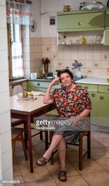 lächelnde ältere frau aus fenster - eine seniorin allein stock-fotos und bilder
