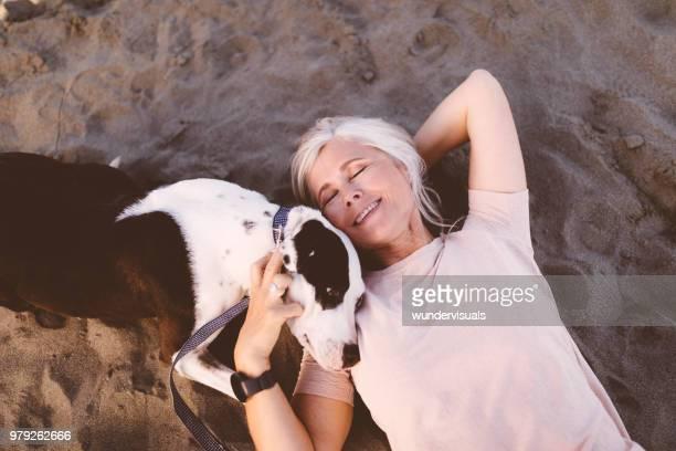 lächelnde ältere frau mit hund am strand liegend - lying down stock-fotos und bilder