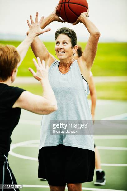 Smiling senior woman making pass during basketball game on outdoor court