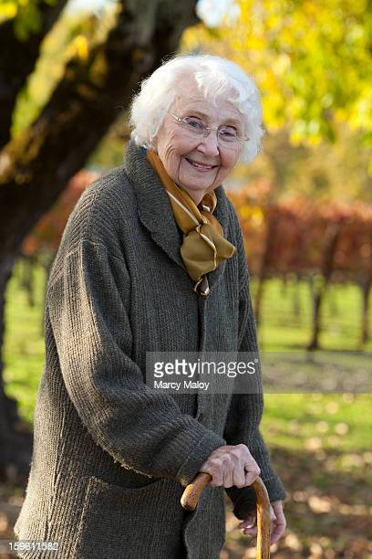 Smiling senior woman outside with a cane.