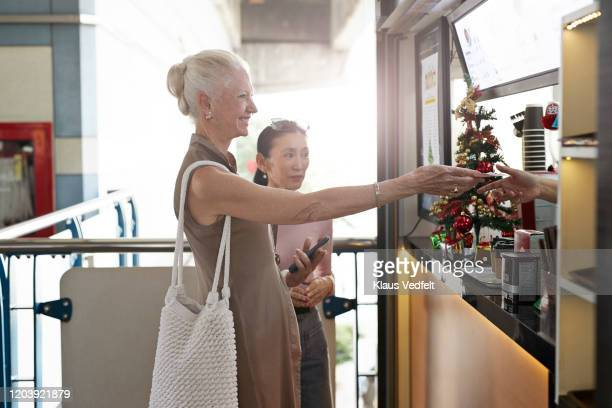 smiling senior woman paying at food restaurant - christmas cash stock pictures, royalty-free photos & images