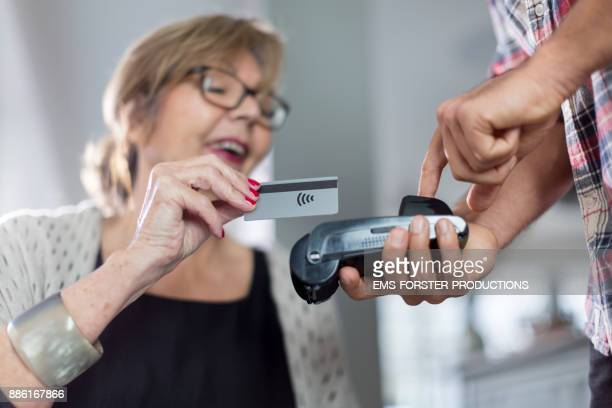 smiling senior woman paying cashless with her credit card