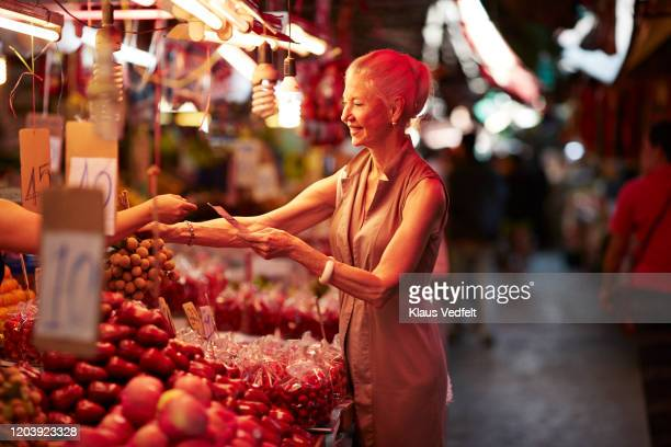 smiling senior woman paying for fruit in market - tourist stock pictures, royalty-free photos & images
