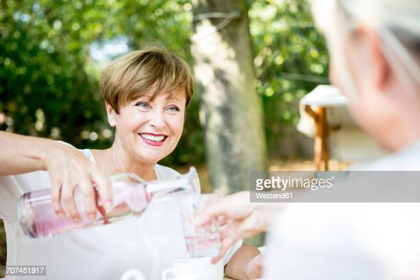Smiling senior woman pouring water into friends glass