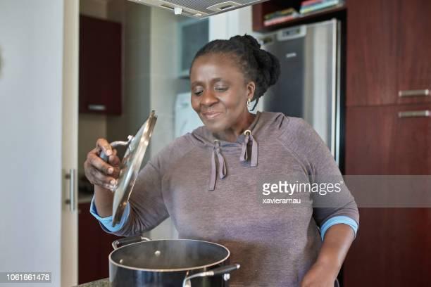 sonriente a mujer senior preparando comida en la cacerola - black cook fotografías e imágenes de stock