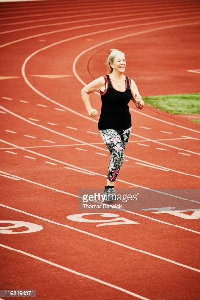 smiling senior woman race walking on track - endurance stock pictures, royalty-free photos & images