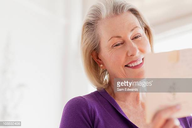 smiling senior woman reading card - greeting card stock pictures, royalty-free photos & images