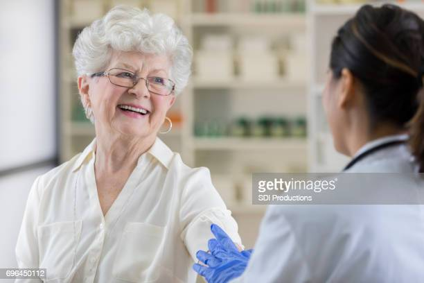 Smiling senior woman receives flu shot from pharmacist