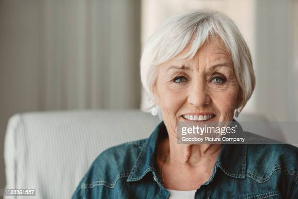 smiling senior woman relaxing at home in the afternoon - senior women stock pictures, royalty-free photos & images